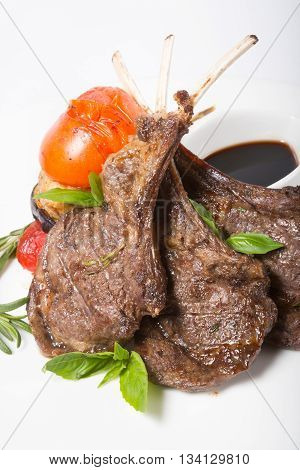 Grilled lamb meat served on a white plate