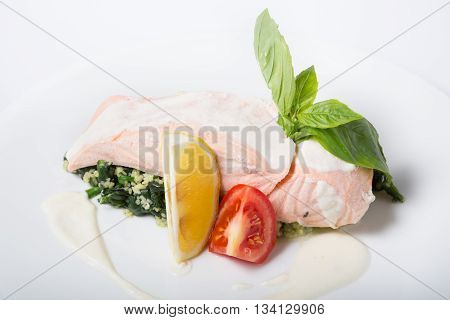 Steamed salmon meat served with lemon and basil