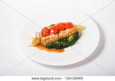 Salmon steak served with broccoli and lemon