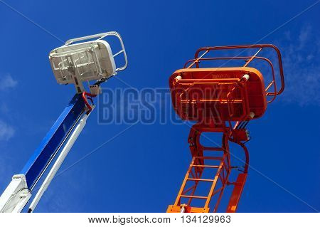Lift platform with bucket and articulating boom with basket of construction hydraulic telescopic cranes, orange and white cherry picker aerial work platforms, heavy industry, blue sky on background
