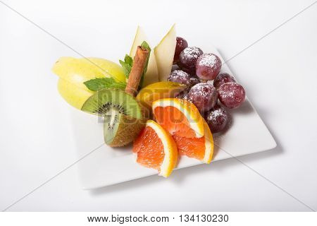 Fresh raw fruits sliced and served on a white plate