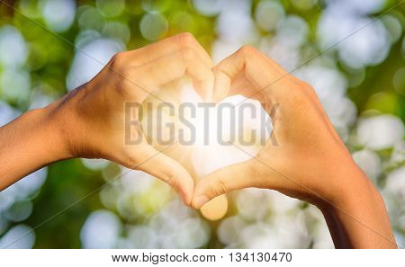 Girl hands in shape of love heart on blurred natural bokeh background