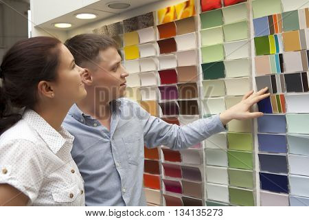 Happy couple family select paint color and look matching samples at household store