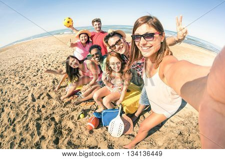 Group of multiracial happy friends taking selfie and having fun with beach sport games - Summer joy concept and multi ethnic friendship - Sunny afternoon color tones with focus on girl holding camera