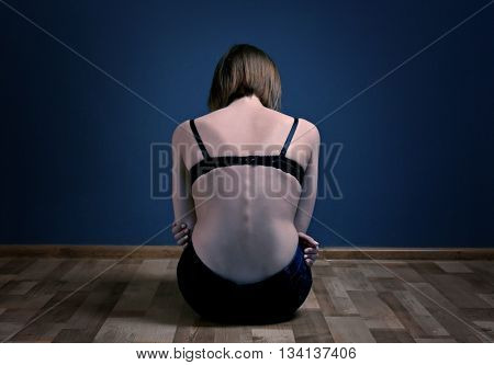 Anorexic girl sitting on the floor on dark wall background