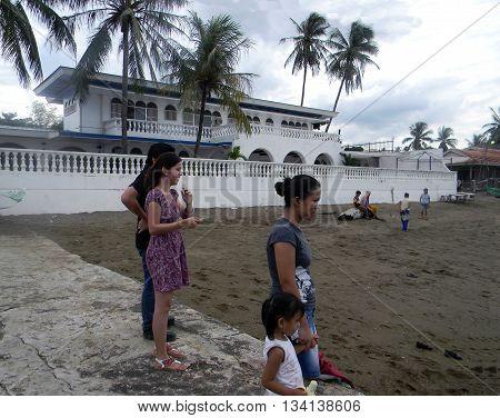 CEBU CITY, CEBU / PHILIPPINES - JULY 30, 2011: People enjoy the beach in front of a large beachfront mansion in Cebu.
