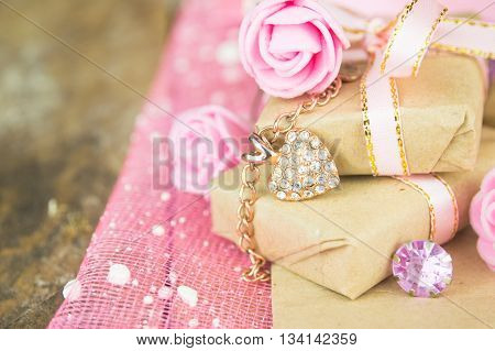 Gift box decor. Wrapped in parchment paper, delicate fresh pink flowers with golden heart