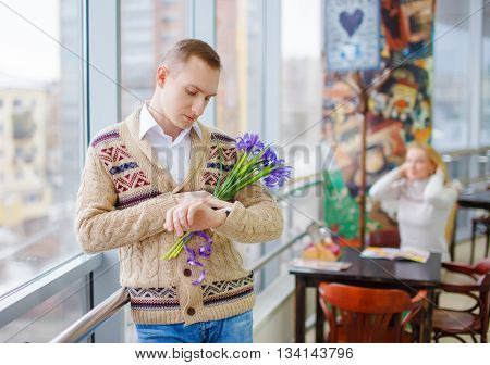 girl wants to get acquainted with a man. the guy holding flowers looks at his watch waiting for his girlfriend. Spice up relationships. Play the strangers game.