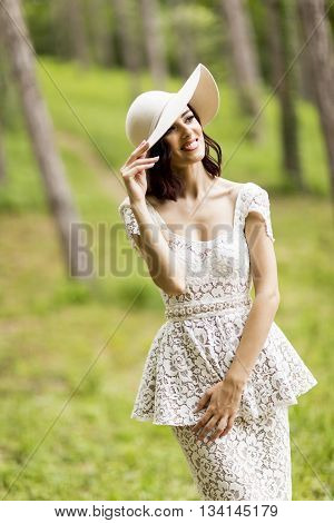 Young Woman Posing In A White Dress With A Hat