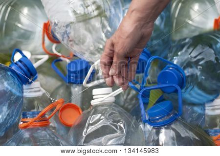 A bunch of water plastic bottles tethered with a steel wire in a female hand