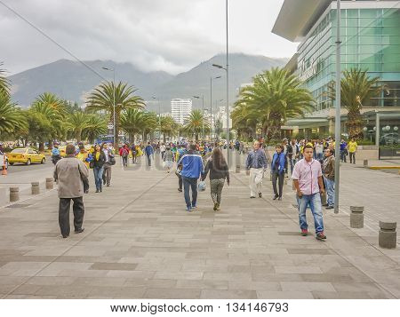 QUITO, ECUADOR, OCTOBER - 2015 - People walking at sidewalk with mountains at background in a modern downtown zone of Quito Ecuador