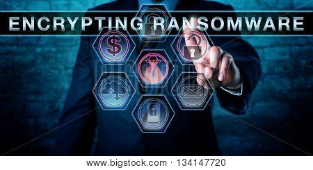 Male malware operator is touching ENCRYPTING RANSOMWARE on a virtual control screen. Computer security concept for a malware attack that is restricting file access via encryption to extort a ransom.