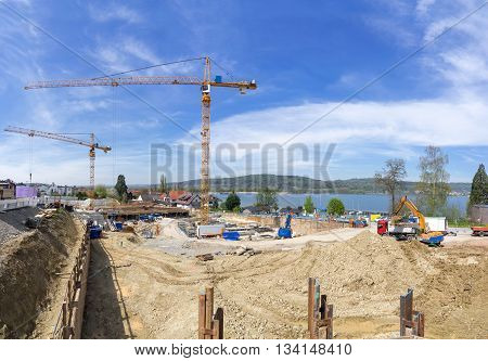 Big construction site with two cranes on a lake. Taken in Bodman at Lake Constance, Germany.