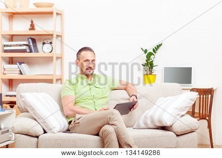 Picture of handsome man using tablet PC at home. Serious man using computer technologies for business purposes.