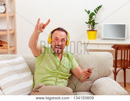 Portrait of handsome man happy listening to music at home. Cheerful man sitting on sofa or couch and showing yo sign to camera.