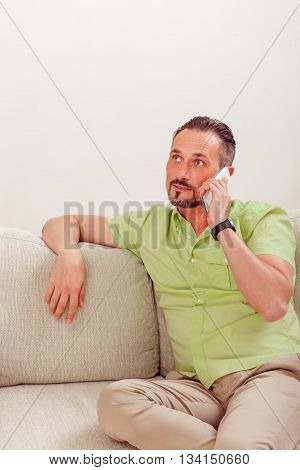 Portrait of handsome man speaking over mobile or smart phone while sitting on sofa or couch at home. Man resting at home.