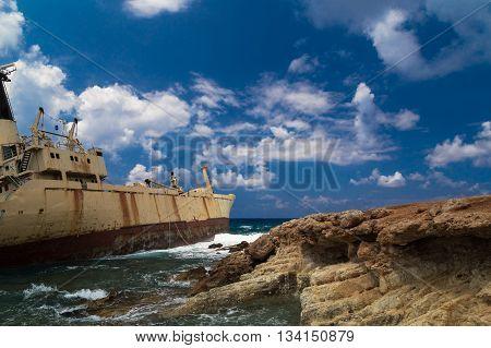 Shipwrecked boat near the rocky shore aground. Mediterranean Sea near Paphos. Cyprus