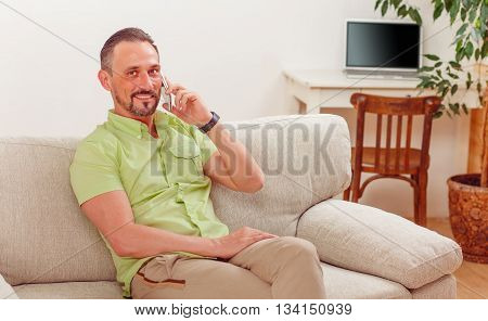 Portrait of handsome man smiling while sitting on sofa or couch and speaking over mobile or smart phone at home.
