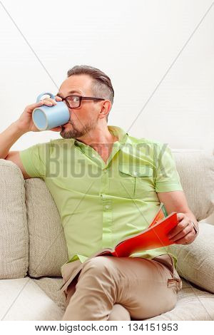 Portrait of handsome man in glasses drinking cup of coffee or tea while sitting on sofa and working with documents from home.
