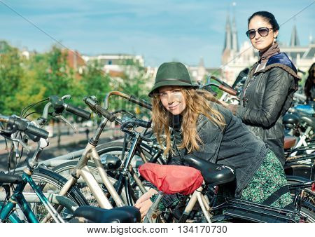 Two women locking their bikes at big cycling parking in Amsterdam, Dutch capital