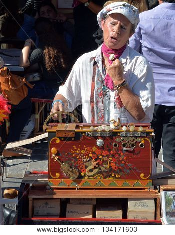 PARIS FRANCE OCT 17 2014: Street artist Arlette Denis (Macadam Manivelle) singing and playing barrel organ at Montmartre. Arlette Denis started singing in 1968.