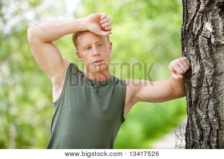Tired man leaning on tree