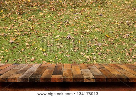Empty wood table top on grass background