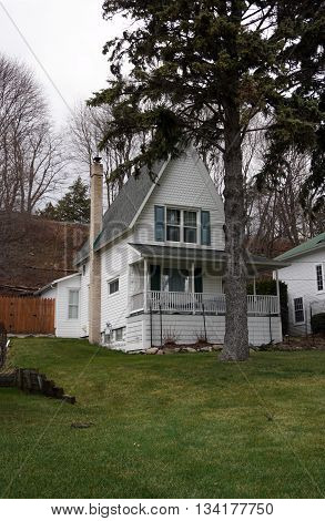 A Victorian home with a wraparound porch and a very steep roof, under the bluff on Fourth Street in Harbor Springs, Michigan, during December.