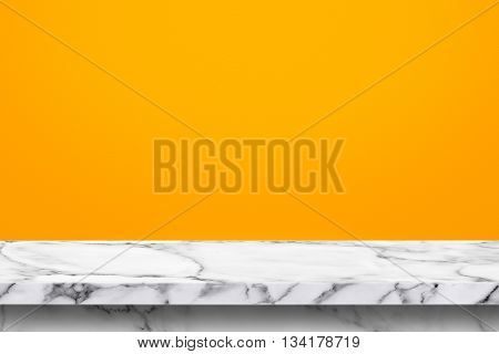 Empty marble stone table with yellow wall background. For display or montage your products.