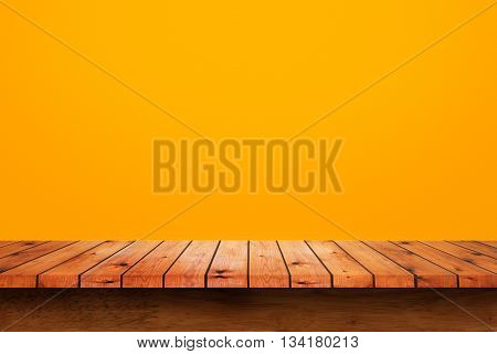 Empty wooden table with yellow wall background. For display or montage your products.