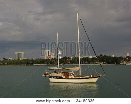 Sailboat Illuminated by a Sunlit Sky and Passing Clouds