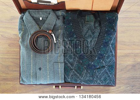 Top View Of Old Suitcase With Clothes On Wooden Floor.