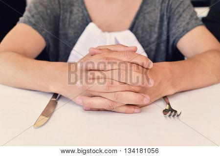 closeup of a young caucasian man sitting at a table waiting for the food, with his hands clasped a and a knife and a fork in front of him
