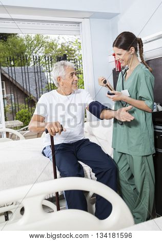 Nurse Checking Blood Pressure Of Patient In Rehab Center