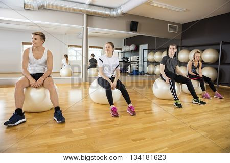 Friends Sitting On Exercise Ball At Gym