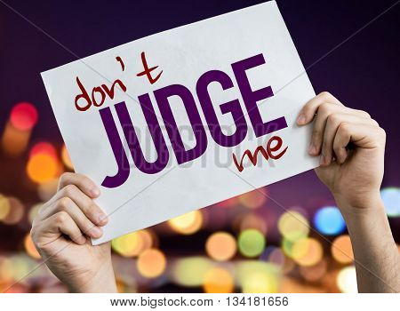 Don't Judge Me placard with night lights on background