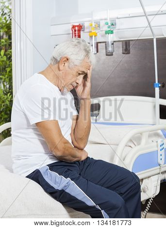 Sad Senior Patient Sitting On Bed At Rehab Center