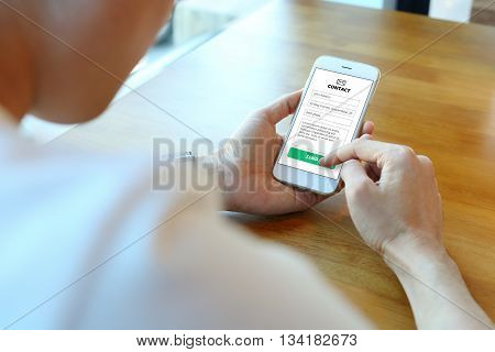 Man holding smartphone with use contact form on website