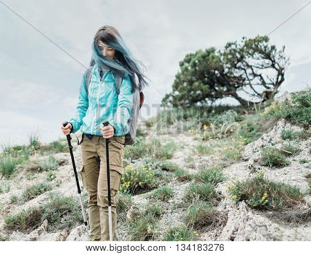 Beautiful hiker young woman with backpack and trekking poles walking in the mountains in summer outdoor