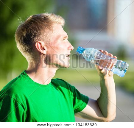 Tired man drinking water from a plastic bottle after fitness time and exercising in city street park at beautiful summer day. Sporty model caucasian ethnicity training outdoor.
