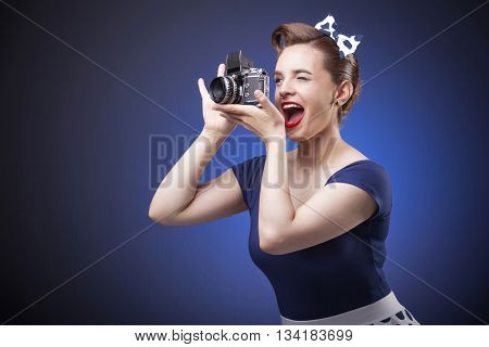 Pin Up girl taking photos with a vintage camera on blue background