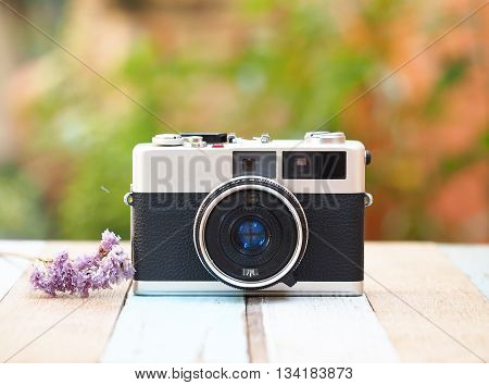 Vintage old camera with flower on the old wooden, focus camera
