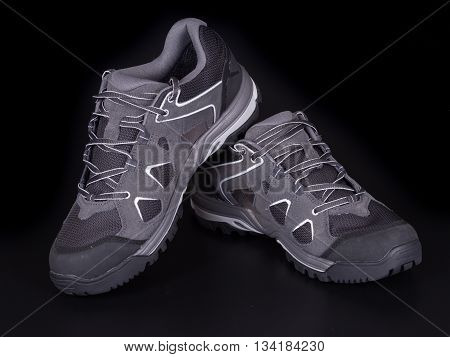 Walking trekking shoes isolated on the black backgroun