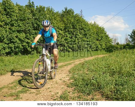 Cyclist on a white bike rides through the forest.