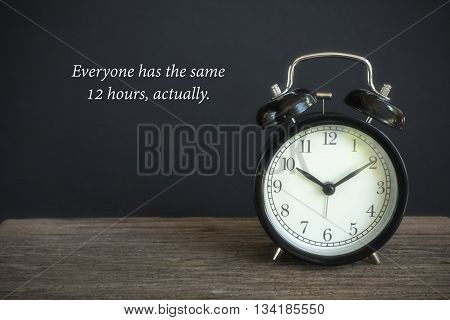 """Alarm clock on wood with a black background. Concept of time with word """"Every one has the same 12 hours"""""""