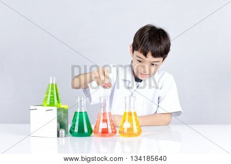 Easy Science experiment for kid the boy has fun when he test acid or color liquid in beaker for education about chemical.