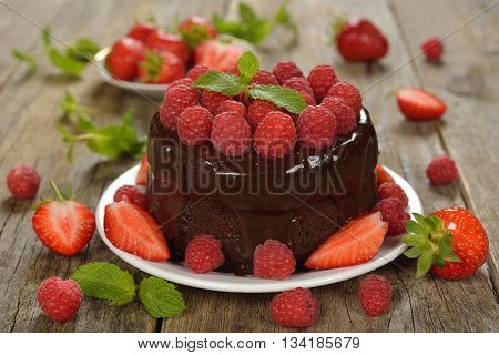 Chocolate cake with raspberries on a wooden background