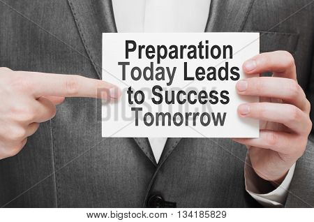 Preparation Today Leads to Success Tomorrow. Business concept written on white card in businessman's hands