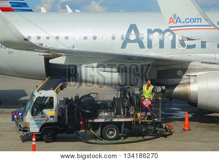 MIAMI, FLORIDA - JUNE 1, 2016: American Airlines worker refueling plane at Miami International Airport. American Airlines operates 274 flights every day from Miami