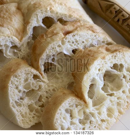 Fresh sliced Turkish bread with a knife.